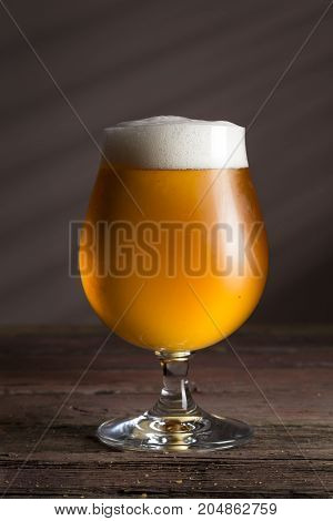 Glass of cold pale beer with a bowl of peanuts on a rustic wooden table. Focus on the foam