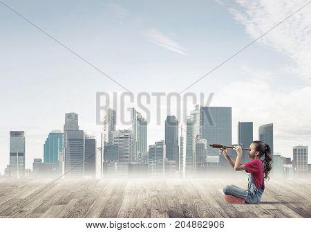 Cute kid girl sitting on wooden floor and looking in spyglass