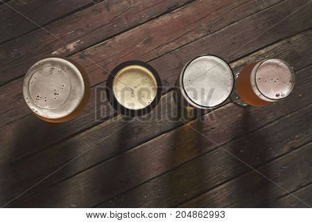 Top view of a pale dark unfiltered pale and red fruit beer in four different beer glasses on a rustic wooden table