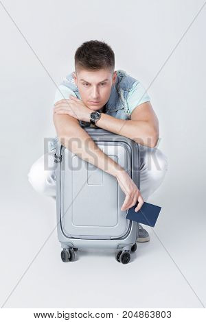 upset young man in denim vest with suitcase against grey background