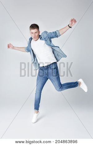 young happy handsome man in jeans and jacket jumping