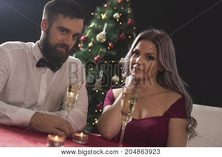 Young attractive couple enjoying romantic Christmas dinner drinking champagne and making a toast.