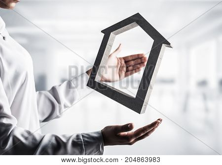 Business woman in white shirt keeping stone house symbol in hands with office view on background. Mixed media.