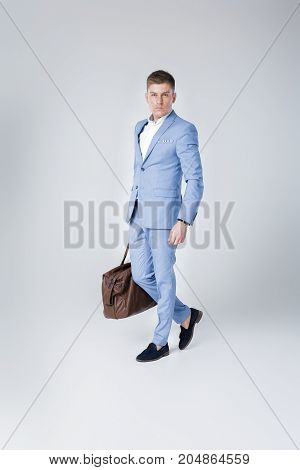 Handsome fashion young man in blue suit holding leather bag and looking at camera against grey background