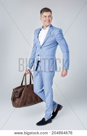 Handsome fashion young man in blue suit holding leather bag and looking away against grey background