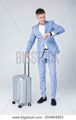 Handsome elegant  young man in blue suit  with suitcase and  looking at watch against grey background