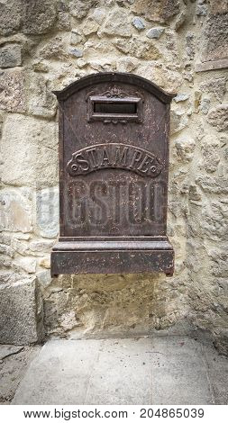 Close up view of an old decaying mailbox hanging on a wall