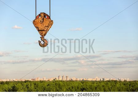 Iron hanging orange crane hook on the background of the green cityscape under the blue sky with clouds. Sun shines onto it. Horizontal.