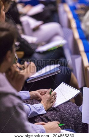 Group of People Making Notes at Conference. Sitting in One Line. Blurred Image.Vertical Image