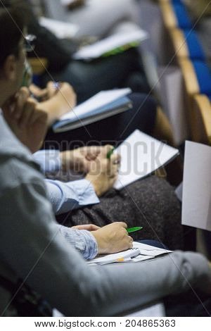 Group of People Making Notes at Conference. Sitting in One Line. Blurred Image.Vertical Image Composition