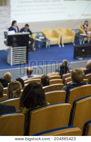 Female Host Speaking at Stage In Front of The Audience During Business Conference in Congress Hall. Concepts of Business and Entrepreneurship.Vertical Image
