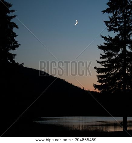 Crescent moon over lake at twilight in late summer