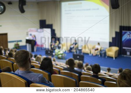 Business Conferences Concept and Ideas. Back of Male Congress Participant Listening to The Lecturer Speaking In front of the Group of People. Horizontal Image Composition