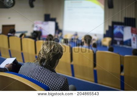 Business Conferences Concept and Ideas. Back of Female Congress Participant Listening to The Lecturer Speaking In front of the Group of People. Horizontal Image Composition