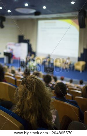 Female Host Speaking at Stage In Front of The Audience During Business Conference in Congress Hall. Ideas of Business and Entrepreneurship.Vertical image Orientation