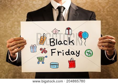 Black Friday text with businessman holding a sign board