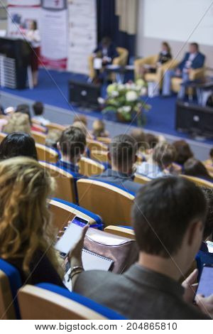 Business Conferences Concept and Ideas. Back of Congress Participants Listening to The Lecturer Speaking In front of the Group of People. Vertical Image Composition