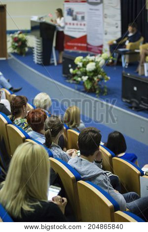Business Conferences Concepts and Ideas. Group of People Attending Conference and Listening to the Host Speaker. Back View.Vertical Image