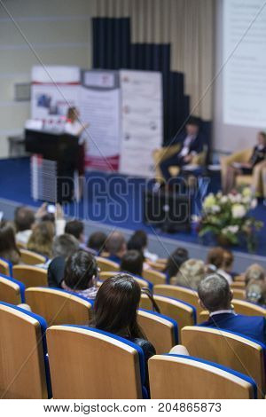 Business Conferences Concepts and Ideas. Group of People Attending Conference and Listening to the Host Speaker. Back View.Vertical Image Composition