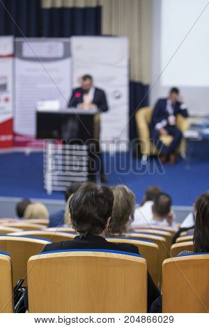Business and Entrepreneurship Congress. Male Speaker Giving a Talk at Business Meeting. Paticipants in Conference Hall. Rear View.Vertical Image Composition