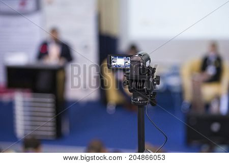 Back View of Compact Videocamera. Positioned Against Blurred Background with Host Speaking on stage. Horizontal Image