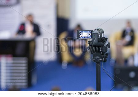 Back View of Compact Videocamera. Positioned Against Blurred Background with Host Speaking on stage. Horizontal Shot