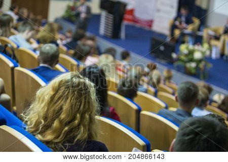 Business Concepts. Male Host Speaking in Front of The Stage To The Audience During Business Conference in Large Congress Hall. Ideas Entrepreneurship. Horizontal image
