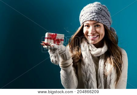 Happy young woman holding a Christmas present