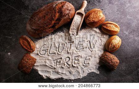 Gluten Free Breads, Glutenfree Word Written And Bread Rolls On Grey Background