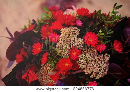 Wedding decoration. Bridal bouquet made of beautiful dark red and magenta flowers.Rich autumn colors.