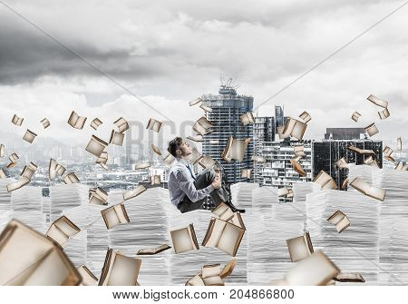 Businessman looking away while sitting on pile of documents among flying books with cityscape on background. Mixed media.