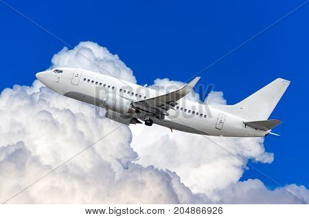 Passenger Airplane Flies In The Sky Climbing Height Above The Cumulus Clouds