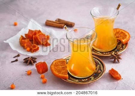Small glasses of autumn yellow tea with swets and honey.