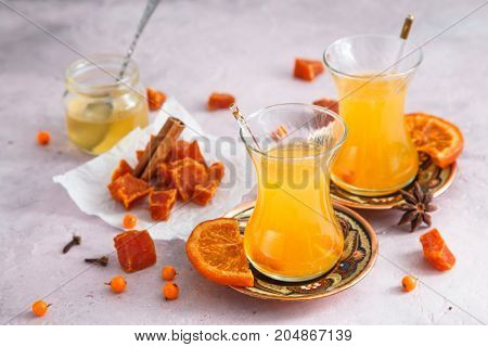 Fruit candies with healthy berries tea in glasses and honey.