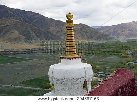 White stupa at Yumbulakhang Palace first building of Tibet on the hill overlooking the rice field of Yarlung valley in Tsetang city - Tibet