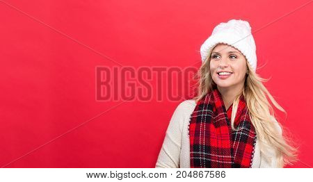Happy young woman in winter clothes on a red background