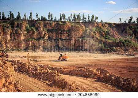 Limestone quarry, construction industry, orange rocks and blue sky