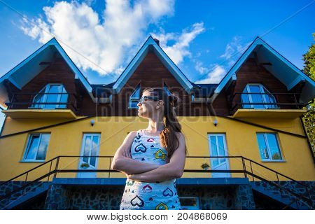 Happy businesswoman standing outside near her new big beautiful home