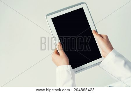 Tablet pc device with blank screen in hands of doctor