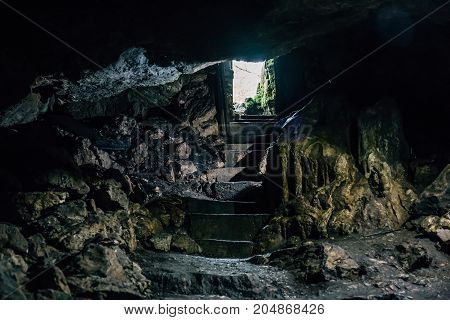 Dark cave with steps of staircase and light from entrance, toned