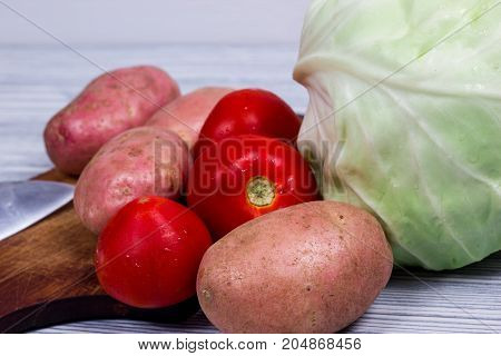 cooking on Kitchen, with potato, knife, cutting board, on wood table
