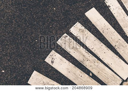 White wooden planks on a shallow black stone surface, top view, abstract background, toned