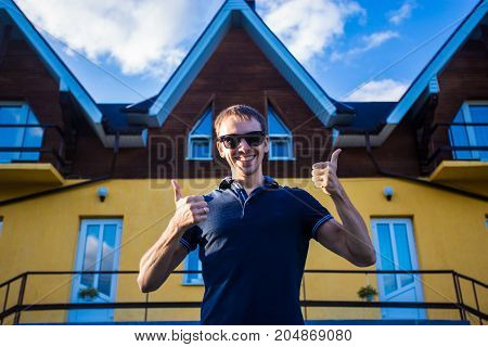 Happy young businessman in sunglasses bought a big home for his family. Man standing with thumbs up standing near his new home
