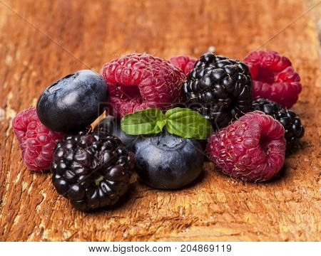 Ripe and sweet berries on wooden table