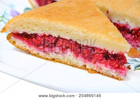 A delicious piece of homemade cake filled with fresh raspberries