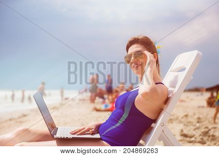Woman with laptop on the beach. Young girl in swimming suit laying on the sun deck looking at something