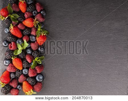 Ripe and sweet berries on black background with copy space