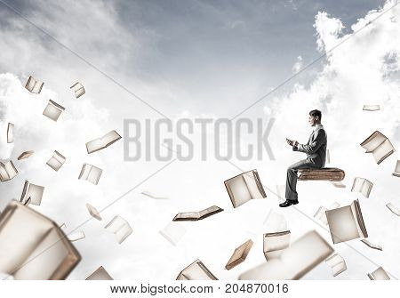 Young businessman floating in blue sky with smartphone in hands