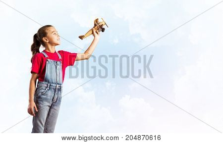 Cute kid girl in overalss with retro plane model in hand