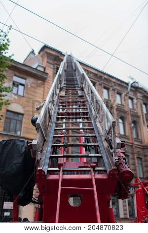 The unfolded ladder fire truck. Firefighters extinguish roof of the old house.
